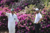 Caddy Adam Hayes, left, gestures beside Jon Rahm, right, as Rahm prepares to putt on the 13th hole during a practice round for the Masters golf tournament in Augusta, Ga., Wednesday, April 7, 2021. (Curtis Compton/Atlanta Journal-Constitution via AP)