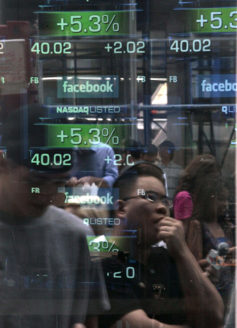 """<p> FILE - In this Friday, May 18, 2012 file photo, passers-by are reflected in the window of the Nasdaq media center as they view reports of trading activity on Facebook's stock on the Nasdaq stock market in New York. The botched offering of Facebook stock has raised several troubling questions, but at least we don't have to worry about the one that plagues most IPOs: How is it that a few select investors were able to pocket obscene profits on a surge in the stock in just a couple of hours? A look at a history of """"pops,"""" and why Facebook's flat debut may not be so bad after all. (AP Photo/Bebeto Matthews, File) </p>"""