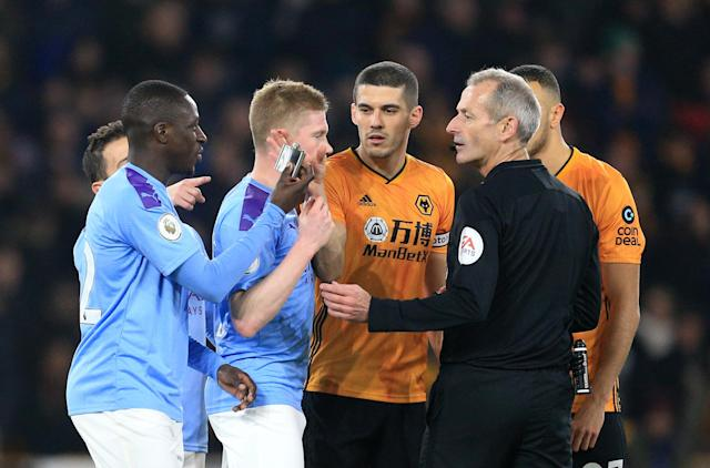 Mendy hands an object thrown onto the pitch to Atkinson (Photo by Matt McNulty - Manchester City/Manchester City FC via Getty Images)