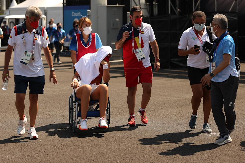 TOKYO, JAPAN - JULY 28: Paula Badosa of Team Spain is helped away from the court in a wheelchair after having to retire from her Women's Singles Quarterfinal match against Marketa Vondrousova of Team Czech Republic on day five of the Tokyo 2020 Olympic Games at Ariake Tennis Park on July 28, 2021 in Tokyo, Japan. (Photo by David Ramos/Getty Images)