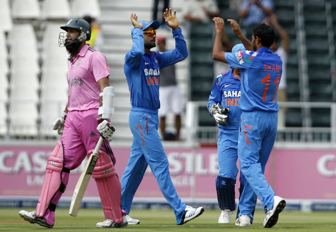 South Africa's Hashim Amla (L) leaves the crease as India's players celebrate his dismissal after he was bowled out by Mohammed Shami during their 1st One-Day International (ODI) in Johannesburg, December 5, 2013. REUTERS/Siphiwe Sibeko (SOUTH AFRICA - Tags: SPORT CRICKET)