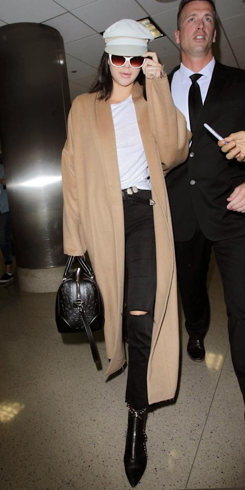 Living every week like it's fashion week, Jenner hit the Tarmac in an ankle-length camel coat, which she paired with a gorgeous set of studded booties, distressed black jeans, a gray newsboy cap, and an embossed leather handbag. The universe is your runway, Kendall!