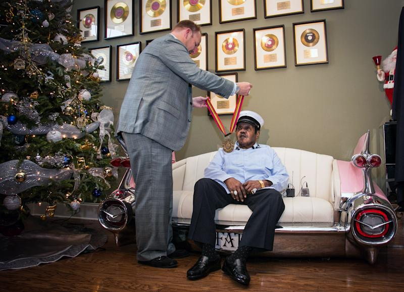 "Legendary musician Fats Domino is named ""Honorary Grand Marshall"" of the Krewe of Orpheus, the star-studded Carnival club that traditionally parades the night before Mardi Gras, Friday, Dec. 20, 2013 in New Orleans. Michael Murphy II of the Krewe of Orpheus presents a medal to Fats Domino.(AP Photo/Doug Parker)."