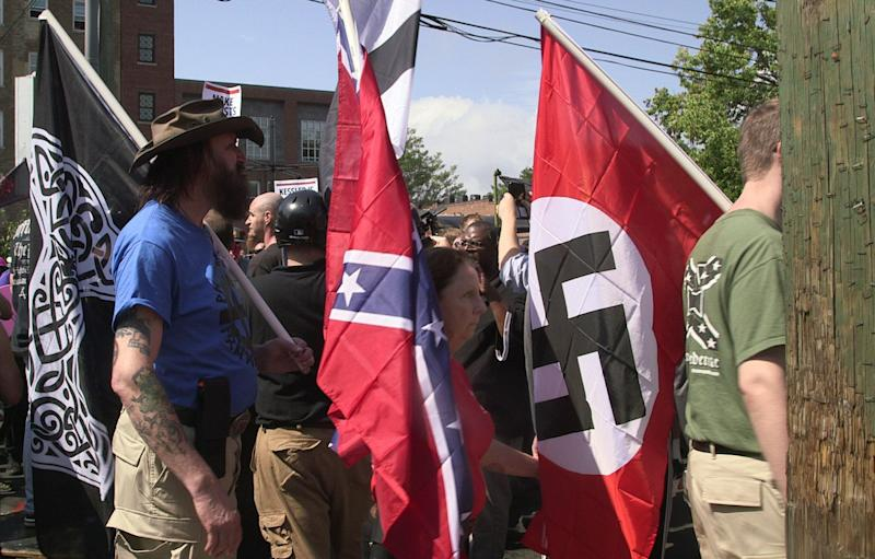 Marchers carry Confederate and Nazi flags during the Unite the Right rally in Charlottesville, Virginia, on Aug. 12, 2017.