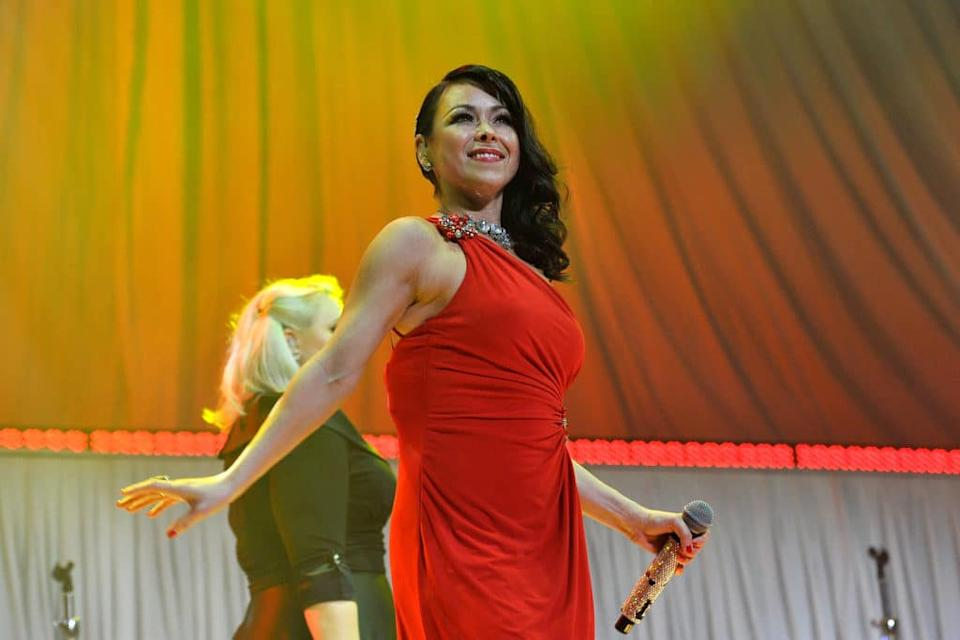 Lisa Scott-Lee performing while wearing a red dress
