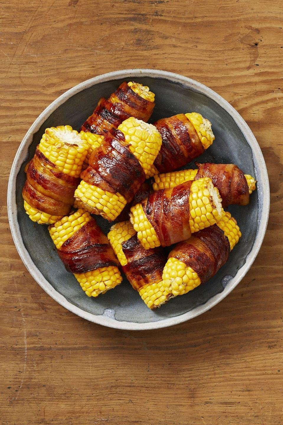 """<p>Like we mentioned, everything is better when it's wrapped in bacon! Here, bacon is tucked around and under itself before baking, ensuring that it shrinks up beautifully around each piece of corn.</p><p><strong><a href=""""https://www.thepioneerwoman.com/food-cooking/recipes/a32905619/bacon-wrapped-corn-on-the-cob-recipe/"""" rel=""""nofollow noopener"""" target=""""_blank"""" data-ylk=""""slk:Get the recipe."""" class=""""link rapid-noclick-resp"""">Get the recipe.</a></strong></p><p><a class=""""link rapid-noclick-resp"""" href=""""https://go.redirectingat.com?id=74968X1596630&url=https%3A%2F%2Fwww.walmart.com%2Fip%2FThe-Pioneer-Woman-Stainless-Steel-12-Inch-Lock-Tongs%2F276114322&sref=https%3A%2F%2Fwww.thepioneerwoman.com%2Ffood-cooking%2Fmeals-menus%2Fg32157273%2Ffourth-of-july-appetizers%2F"""" rel=""""nofollow noopener"""" target=""""_blank"""" data-ylk=""""slk:SHOP TONGS"""">SHOP TONGS</a></p>"""