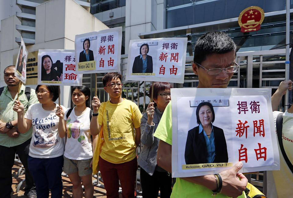 FILE - In this Friday, April 17, 2015 file photo, anti-Beijing protesters hold pictures of jailed veteran Chinese journalist Gao Yu during a rally outside Chinese central government's liaison office in Hong Kong. In a report by the Committee to Protect Journalists, the group said that after Turkey, the worst offender in 2016 was China, where 38 journalists were in custody on Dec. 1. China had jailed the most journalists worldwide in the previous two years. (AP Photo/Kin Cheung, File)