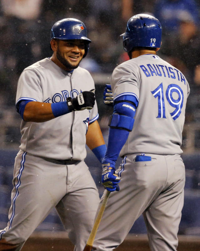 Toronto Blue Jays' Melky Cabrera, left, is congratulated by teammate Jose Bautista (19) after scoring on a wild pitch by Kansas City Royals starting pitcher Jason Vargas during the fifth inning of a baseball game in Kansas City, Mo., Tuesday, April 29, 2014. Cabrera also drove in a run during the inning. (AP Photo/Orlin Wagner)