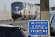 A sign is shown at a railroad crossing, Sunday, Sept. 26, 2021, near to cars from an an Amtrak train that derailed Saturday just west of Joplin, Mont. The westbound Empire Builder was en route to Seattle from Chicago, with two locomotives and 10 cars. (AP Photo/Ted S. Warren)