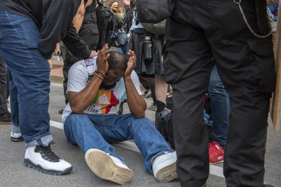 In this Sept. 25, 2020 photo, a man reacts after the Louisville Police Department fired flash-bang grenades into a crowd of protesters. Chief Robert Schroeder said during a news conference the police used the grenades to get the crowd's attention to provide direction on how to disperse. (Isabel Miller via AP)