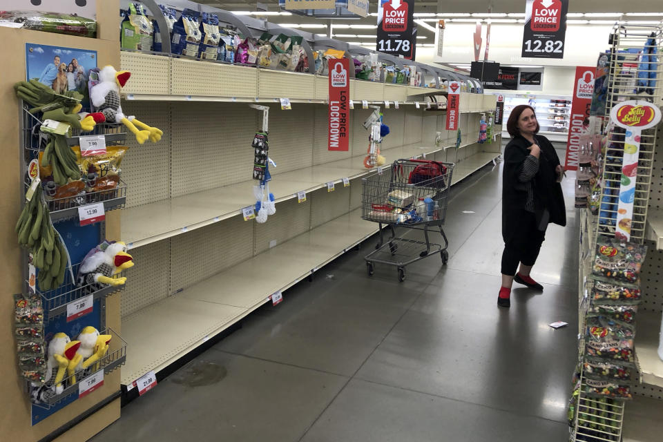 A woman shops near empty shelves at a Hy-Vee food store Friday, March 13, 2020, in Overland Park, Kan. (AP Photo/Charlie Riedel)