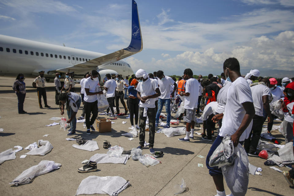 Haitians deported from the United States recover their belongings scattered on the tarmac of the Toussaint Louverture airport in Port-au-Prince, Haiti Tuesday, Sept. 21, 2021 (AP Photo/Joseph Odelyn)