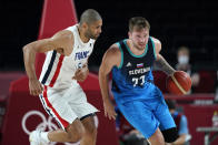 Slovenia's Luka Doncic (77) drives up court past France's Nicolas Batum (5) during a men's basketball semifinal round game at the 2020 Summer Olympics, Thursday, Aug. 5, 2021, in Saitama, Japan. (AP Photo/Charlie Neibergall)