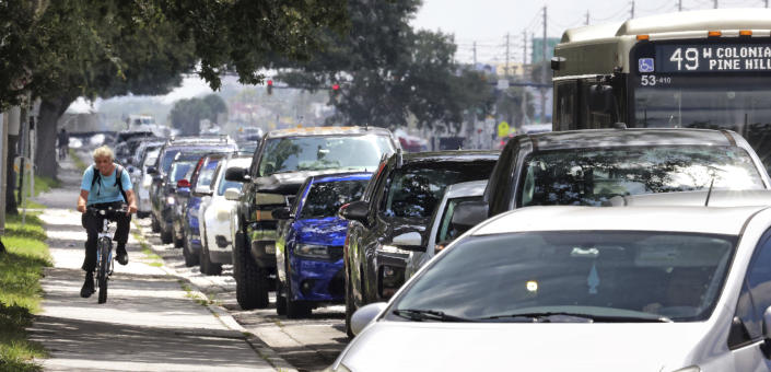 A cyclist passes cars at a standstill along West Colonial Drive in Orlando, Fla., Thursday, July 29, 2021, as residents wait in line for COVID-19 testing at Barnett Park. The line stretched through the park for more than a mile to the entrance to the Central Florida Fairgrounds. Orange County is under a state of emergency as coronavirus infections skyrocket in Central Florida. The Barnett Park site is testing 1,000 people a day and has closed early in recent days due to reaching capacity. (Joe Burbank/Orlando Sentinel via AP)