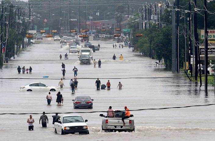 <p>People walk through the flooded waters of Telephone Rd. in Houston on Aug. 27, 2017 as the U.S. fourth city city battles with tropical storm Harvey and resulting floods. (Photo: Thomas B. Shea/AFP/Getty Images) </p>