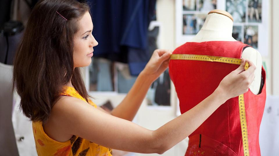 96 Money-Making Skills You Can Learn in Less Than a Year, Fashion designer measuring a dress. Shallow depth of field.
