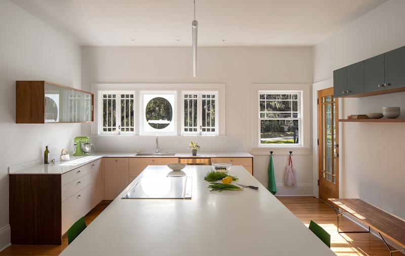 """AFTER: """"We removed a wall to accommodate a large island and connect the space to the living area,"""" says Jody. """"I love the combination of the minimalist cabinets with the historic window casings and moldings. One of the home's previous owners was a sea captain, and he created an etching of his favorite ship on one of the kitchen windows."""" The cabinets are Space Theory by Henrybuilt, the countertop is Corian, and the stools are from BluDot."""