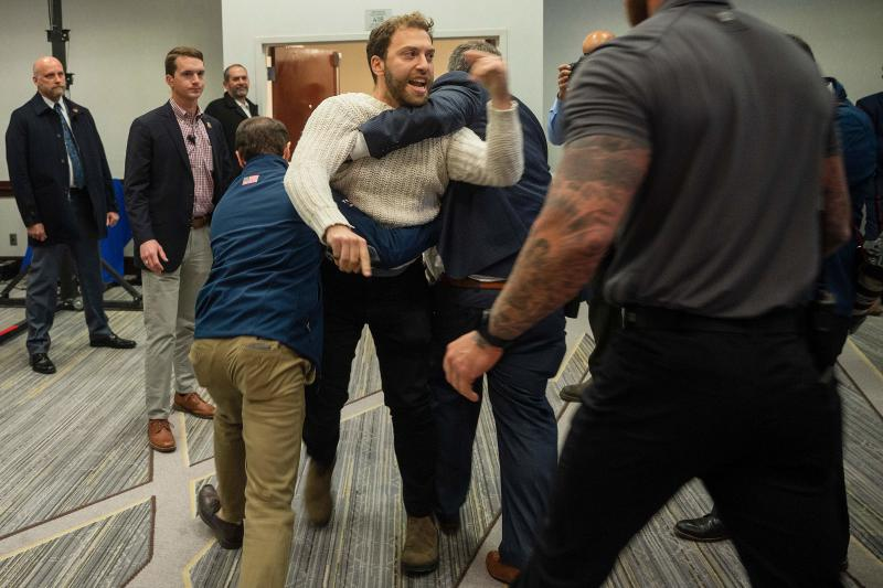 """A protester is dragged from the room as Donald Trump Jr. speaks with his brother Eric during a """"Keep Iowa Great"""" press conference in Des Moines, IA, on February 3, 2020. (Jim Watson/AFP via Getty Images)"""