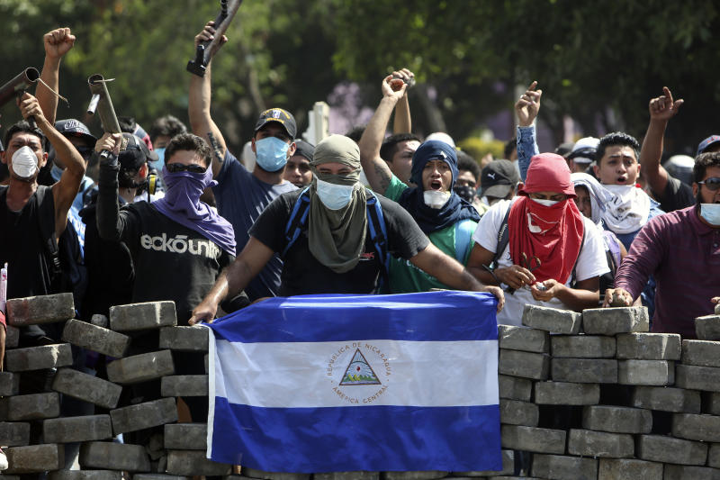 Masked protesters, one with a Nicaraguan flag, yell from the road block they erected as they face off with security forces near the University Politecnica de Nicaragua (UPOLI) in Managua, Nicaragua, Saturday, April 21, 2018. Nicaragua's government said on Saturday it is willing to negotiate over controversial social security reforms that have prompted protests and deadly clashes this week. (AP Photo/Alfredo Zuniga)