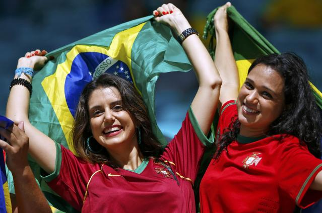 Fans of Portugal hold Brazilian flags as they wait for the start of the 2014 World Cup Group G soccer match between Germany and Portugal at the Fonte Nova arena in Salvador June 16, 2014. REUTERS/Darren Staples (BRAZIL - Tags: SOCCER SPORT WORLD CUP)