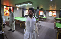 Mohammad Ikram, who play snooker with his chin, walks at a local snooker club in Samundri town, Pakistan, Sunday, Oct. 25, 2020. Ikram, 32, was born without arms, but everyone simply admires his snooker skills when he hits the cue ball with his chin and pots a colored ball on a snooker table. He lives in a remote rural town of Punjab province and his physical disability doesn't come in his way to fulfill his childhood dream of playing the game of snooker. (AP Photo/Anjum Naveed)