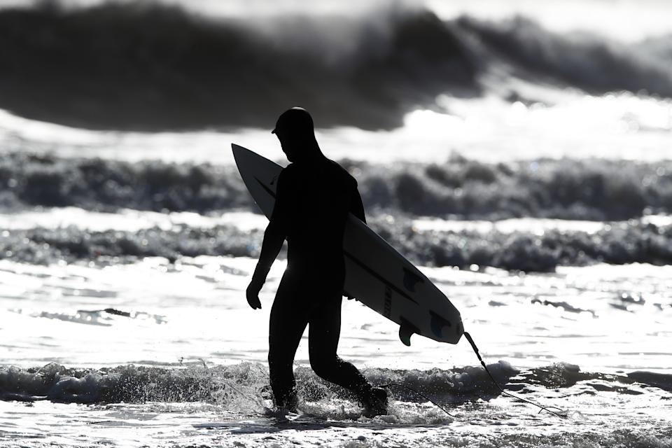 A surfer wades in to defy the lockdown in Tynemouth (Owen Humphreys/PA)