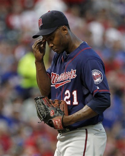 Minnesota Twins starting pitcher Samuel Deduno wipes his forehead after hitting Texas Rangers' Elvis Andrus with a pitch in the second inning of a baseball game Friday, Aug. 24, 2012, in Arlington, Texas. (AP Photo/Tony Gutierrez)