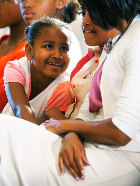 Younger daughter Sasha (L) talks with first lady Michelle Obama (R) daughter Malia (C) looks on during a concert at the East Room of the White House June 15, 2009 in Washington, DC. The first lady launched the White House music series with a jazz studio including a classroom session and a concert featuring Wynton Marsalis, Paquito D'Rivera and Tony Madruga. Obama's other also attended the event. (Photo by Alex Wong/Getty Images)