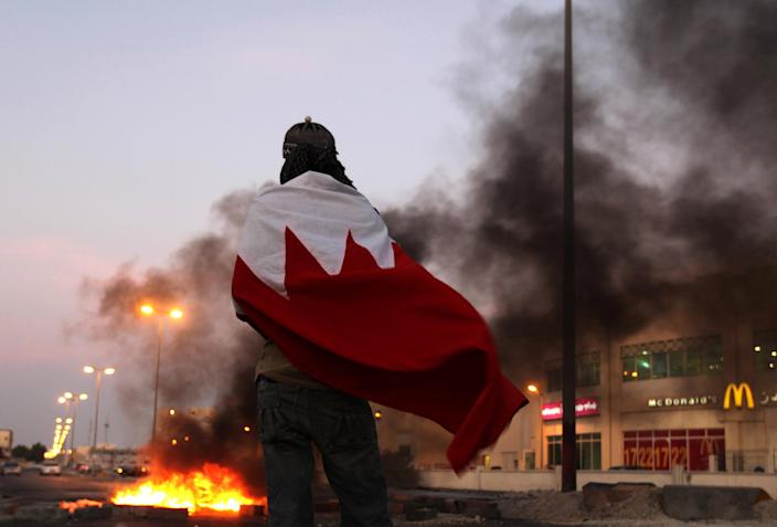 """A Bahraini anti-government protester wearing a national flag watches for riot police as tires burn on a street in the western village of Malkiya, Bahrain, on Tuesday, Aug. 13, 2013. Inspired by the movement behind Egypt's military coup, pro-democracy activists in Bahrain are hoping to gain new momentum by calling for nationwide protests Wednesday. Authorities warned they will """"forcefully confront"""" any large demonstrations, raising fears of more violence in the strategic Gulf kingdom. (AP Photo/Hasan Jamali)"""