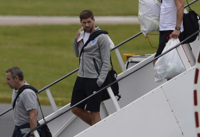 England's Steven Gerrard (C) arrives back from the 2014 World Cup in Brazil at Manchester airport, northern England June 25, 2014. REUTERS/Nigel Roddis (BRITAIN - Tags: SPORT SOCCER WORLD CUP)