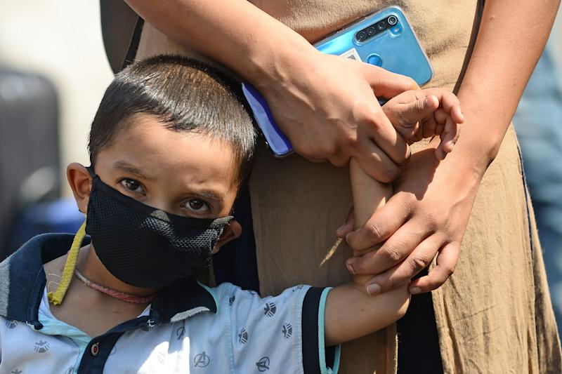 A child stands in a queue while holding hands of his mother outside the entrance of railway station in New Delhi on May 12, 2020. - India's enormous railway network was grinding back to life on May 12 as a gradual lifting of the world's biggest coronavirus lockdown gathered pace even as new cases surged. The country of 1.3 billion imposed a strict shutdown in late March, which Prime Minister Narendra Modi's government has credited with keeping cases to a modest 70,000, with around 2,000 deaths. (Photo by Sajjad HUSSAIN / AFP) (Photo by SAJJAD HUSSAIN/AFP via Getty Images)