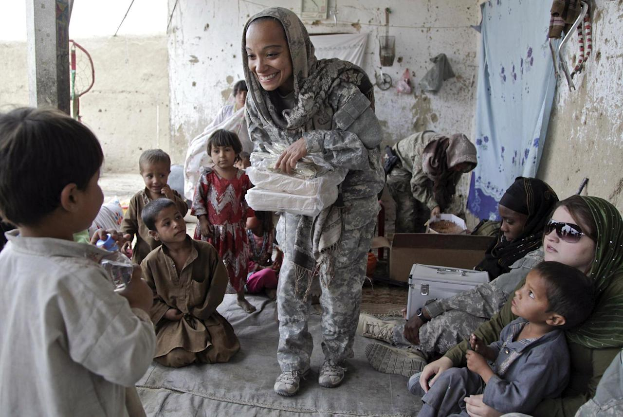 In this image released by the Defense Department, a team leader for a U.S. Special Operations Cultural Support Team, hands out utensils during a women's shura held at a local compound in the village of Oshay, Uruzgan province, Afghanistan, May 4, 2011. With the support of U.S. special operation forces, the CST and Female Treatment Team are working closely together in order to bring health education to women in the area, as well as give them a voice in the district. (AP Photo/DoD)