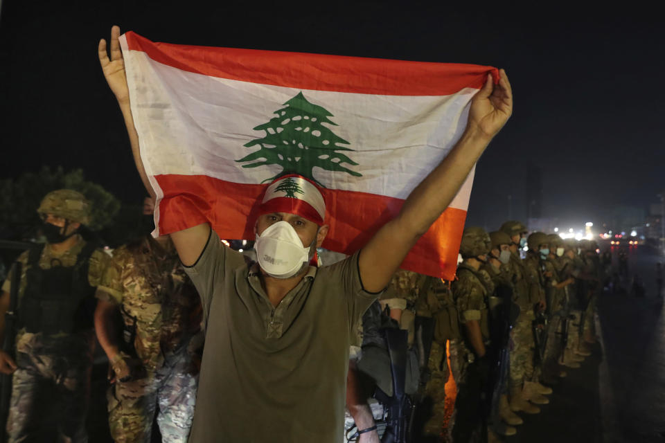 An anti-government protester holds up a Lebanese flag as army soldiers stand guard during a demonstration against deteriorating economic conditions as politicians are deadlocked over forming a new government, in the town of Jal el-Dib, north of Beirut, Lebanon, Sunday, Sept. 27, 2020. Lebanese Prime Minister-designate Mustapha Adib resigned Saturday amid a political impasse over government formation, dealing a blow to French President Emmanuel Macron's efforts to break a dangerous stalemate in the crisis-hit country. (AP Photo/Bilal Hussein)