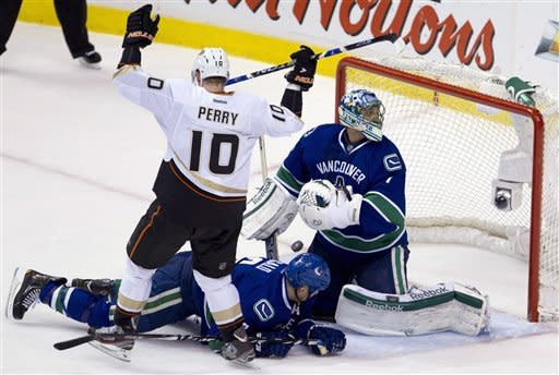 Anaheim Ducks right wing Corey Perry (10) celebrates his goal as Vancouver Canucks goalie Roberto Luongo (1) and defenseman Sami Salo (6) look on during first period NHL hockey action at Rogers Arena in Vancouver, British Columbia, Tuesday, April, 3, 2012. (AP Photo/The Canadian Press, Jonathan Hayward)