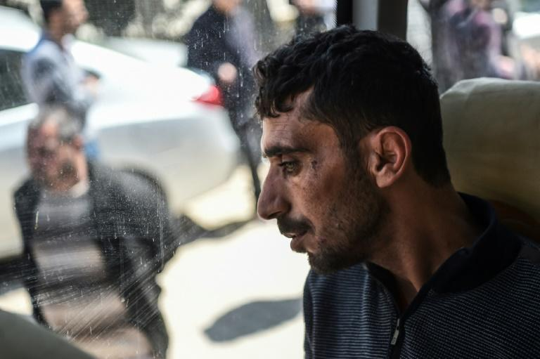 A man looks on in a bus carrying Syrian victims of suspected chemical attack back to the Syrian border after treatment at Reyhanli hospital in Hatay on April 7, 2017