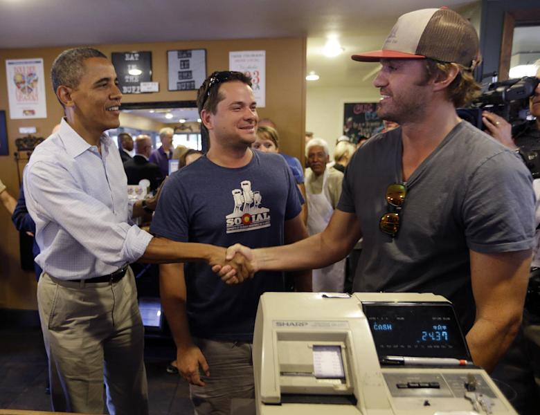 President Barack Obama, left, greets patrons during an unscheduled stop at the Buff Restaurant, Sunday, Sept. 2, 2012, in Boulder, Colo. (AP Photo/Pablo Martinez Monsivais)