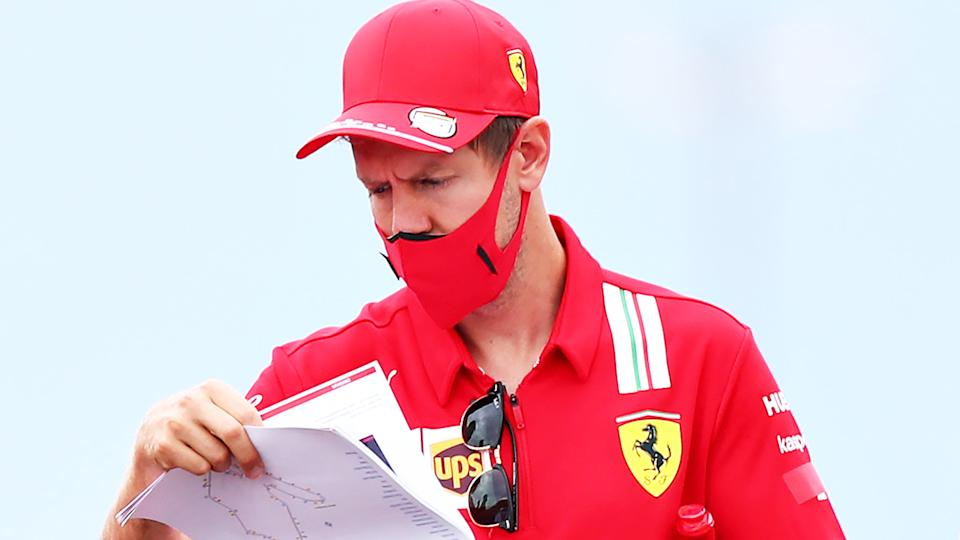 Ferrari driver Sebastian Vettel is pictured looking at notes ahead of the Hungarian Grand Prix.