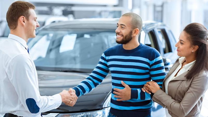 Couple buying new car shaking hands with salesman at car dealership