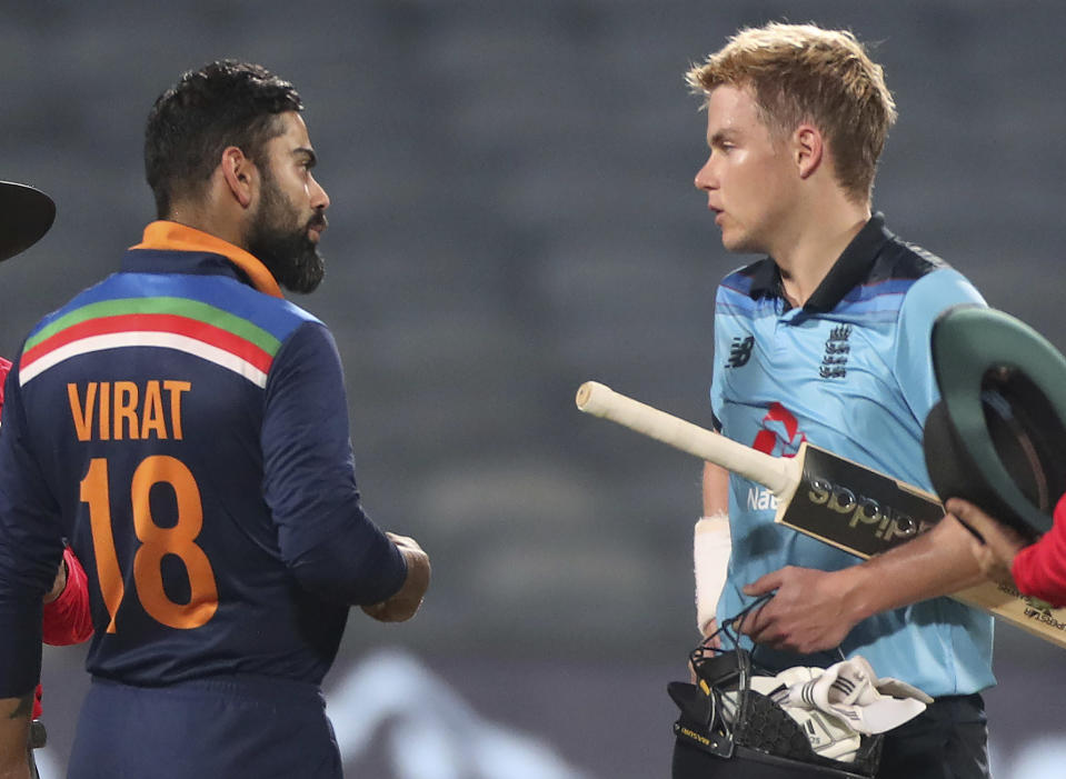 India's captain Virat Kohli, left, interacts with England's Sam Curran at the end of the third One Day International cricket match between India and England at Maharashtra Cricket Association Stadium in Pune, India, Sunday, March 28, 2021. (AP Photo/Rafiq Maqbool)