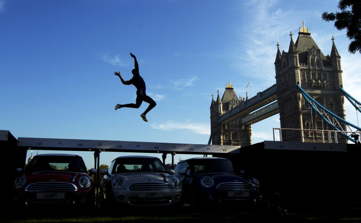 Current British long jump champion J.J. Jegede is silhouetted as he performs an exhibition jump over three Mini cars backdropped by Tower Bridge in London, Wednesday, Sept. 28, 2011. The event took place Wednesday to mark the launch of the Mini London 2012 edition models, of which 2,012 will be produced ahead of the London 2012 Olympic Games. (AP Photo/Matt Dunham)