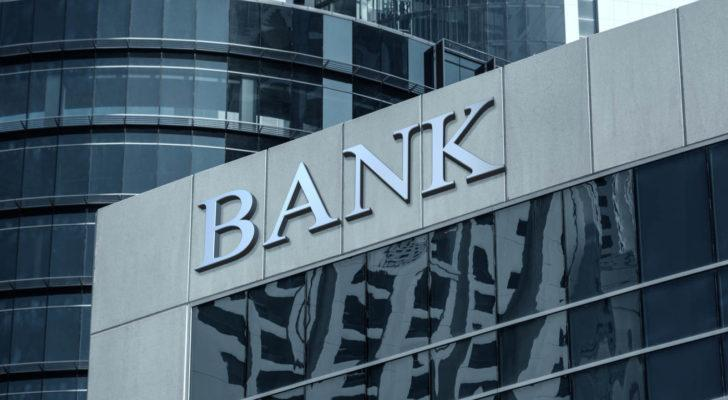 Image of a grey cityscape with a large corporate building that features the word bank on it