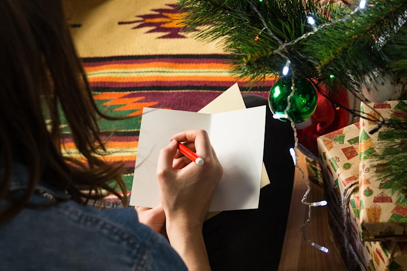 Young female signs postcard sitting on floor next to decorated fur tree and pile of new year presents packaged in beautiful packpaper
