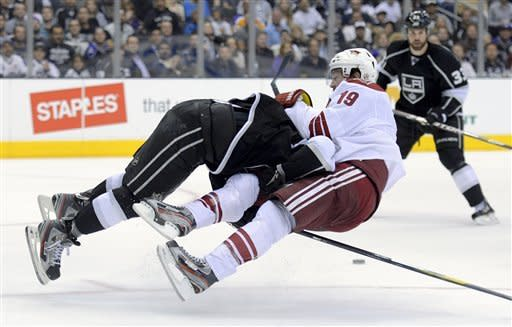 Los Angeles Kings defenseman Drew Doughty, left, knocks Phoenix Coyotes right wing Shane Doan off the puck as defenseman Willie Mitchell watches during the third period of Game 3 of the NHL hockey Stanley Cup Western Conference finals, Thursday, May 17, 2012, in Los Angeles. The Kings won 2-1. (AP Photo/Mark J. Terrill)