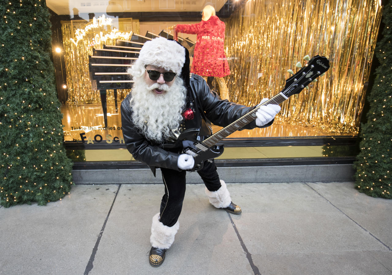 <p>A rock-n-roll Santa plays the guitar outside Selfridges as the store unveils its 2018 Christmas window display 'Selfridges Rocks Christmas'. (John Phillips/Getty Images) </p>