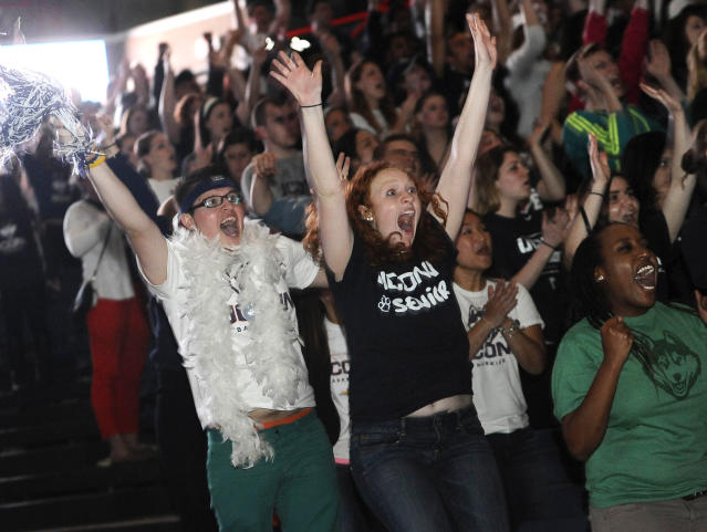 Husein Becirovic of New Britain, Conn., left, Laura Purcell of Stoughton, Mass., center, and Yvonne Ambenge of Mansfield, Conn., right, cheer as they watch the broadcast of the UConn and Notre Dame women's basketball game for the NCAA title, Tuesday, April 8, 2014, in Storrs, Conn. (AP Photo/Jessica Hill)