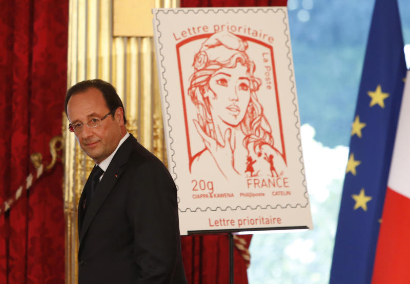 FILE - In this Sunday, July 14, 2013 file photo French President Francois Hollande stands next to the newly unveiled official Marianne postage stamp at the Elysee Palace during the Bastille Day celebrations in Paris. The new face of France _ or at least the official postage stamp for the President Francois Hollande era _ is modeled after a Ukrainian woman who takes her top off to defend feminist causes. Not everyone thinks that's appropriate. The small, conservative Christian Democrat Party is calling for a boycott of the stamp. Hollande on Sunday unveiled the new stamp, meant to represent Marianne, a symbol of France since the revolution. Afterward, the artist said the image was modeled largely after Femen activist Inna Shevchenko. (AP Photo/Francois Mori, File)