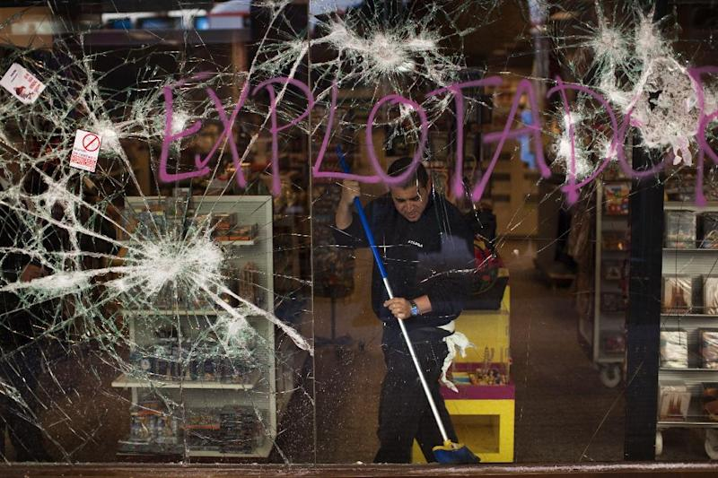 A worker cleans a shop stormed by demostrators following clashes between police and protesters after a general strike in Barcelona, Spain, Friday, March 30, 2012. The Spanish government prepared to approve on Friday a new austerity budget that hundreds of thousands protested against this week in sometimes violent demonstrations. (AP Photo/Emilio Morenatti)