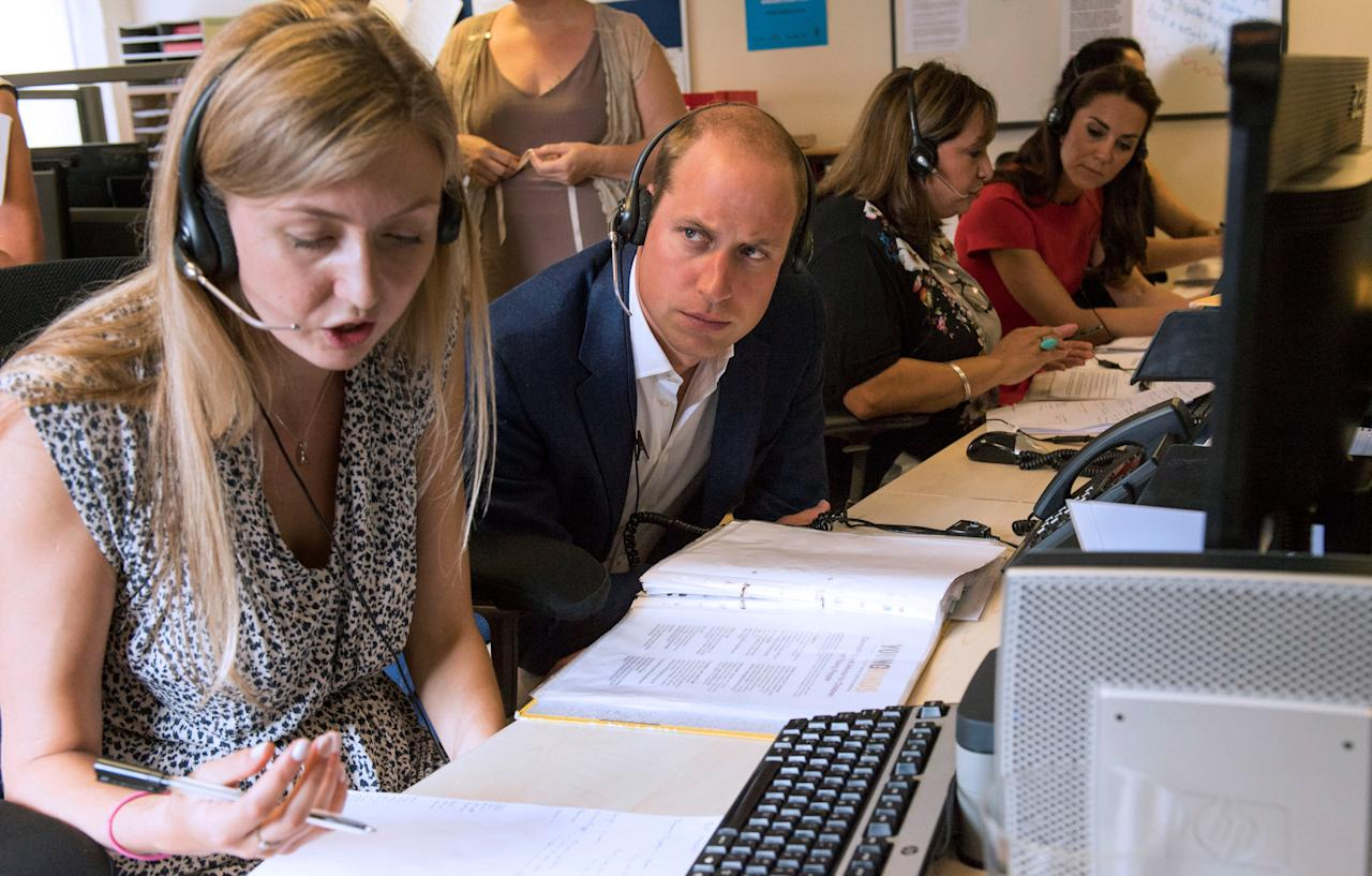 Britain's Prince William (2nd  L), listens on a set of headphones during a visit to a helpline service, as part of a Heads Together campaign in London, Britain, August 25, 2016. REUTERS/Arthur Edwards/Pool