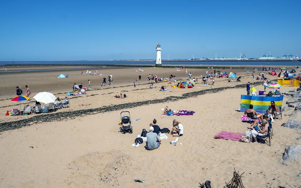 Sunbathers make the most of the mini heatwave in New Brighton, Wirral, on what could be the hottest day of the year. Picture date: Saturday July 17, 2021.
