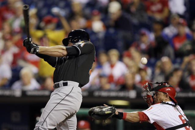 Philadelphia Phillies catcher Carlos Ruiz, right, is hit in the face mask on a strike to Miami Marlins' Justin Ruggiano during the first inning of a baseball game, Wednesday, Sept. 18, 2013, in Philadelphia. (AP Photo/Matt Slocum)